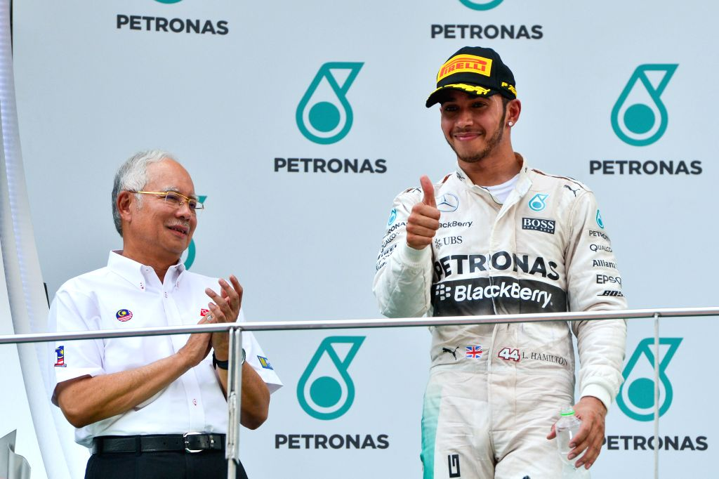 Malaysian Prime Minister Najib Razak (L) applauds as Mercedes driver Lewis Hamilton of Britain gestures on the podium after the Malaysian Formula One Grand Prix in ... - Najib Razak