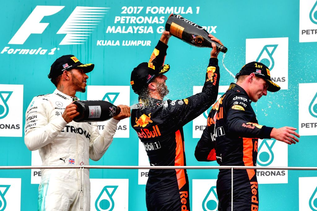 SEPANG, Oct. 1, 2017 - Mercedes driver Lewis Hamilton (L) of Britain and Red Bull driver Daniel Ricciardo (C) of Australia pour champagne on Red Bull driver Max Verstappen of the Netherlands on the ...
