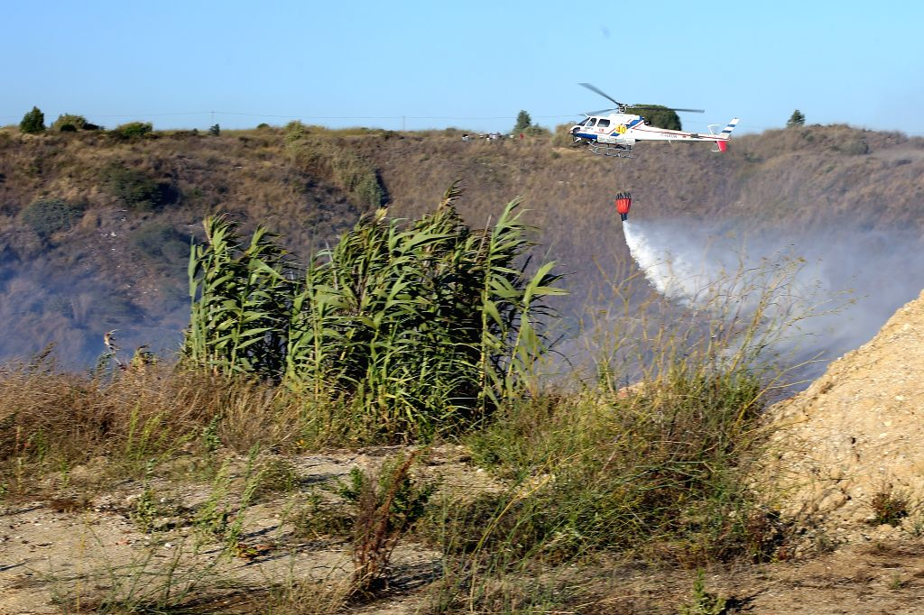 SESIMBRA, Aug. 3, 2019 - A firefighting helicopter drops water on a fire in Sesimbra, Portugal, Aug. 2, 2019.