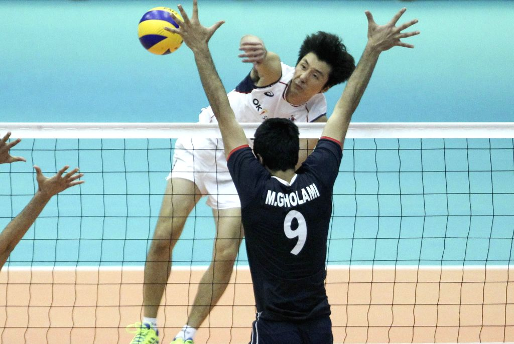 Seungsuk Kwak (top) of South Korea spikes the ball during the match against Iran at the 18th Asian Men's Volleyball Championship at Azadi Stadium in Tehran, Iran, on ...
