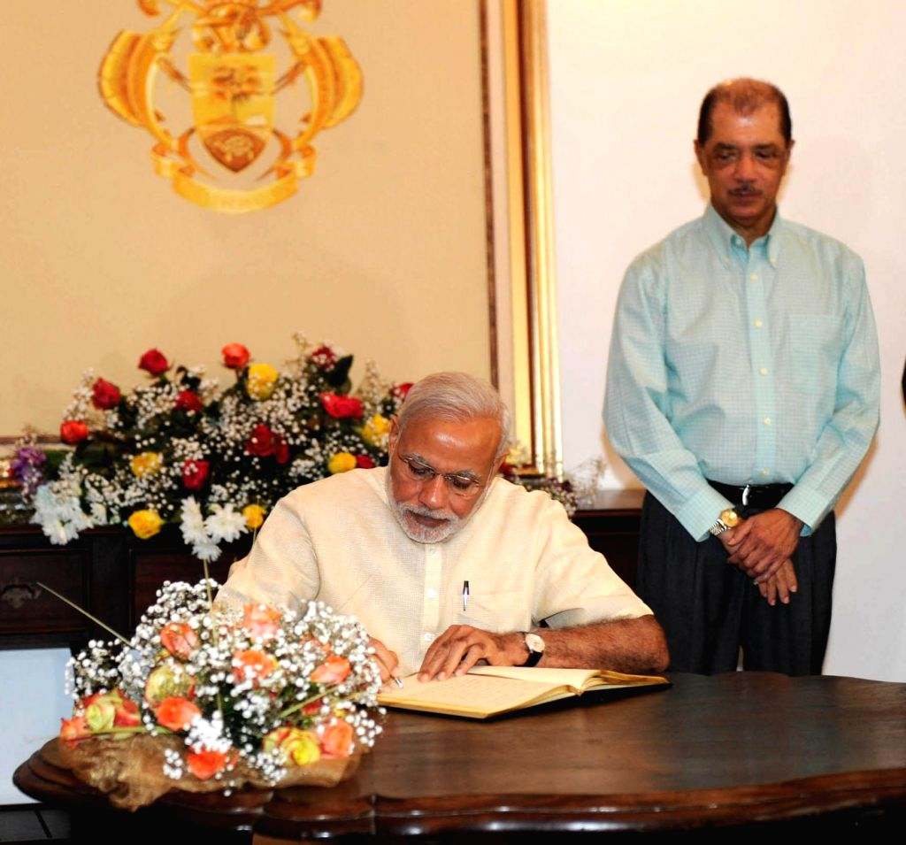 Prime Minister Narendra Modi signs the visitor's book after the Ceremonial Reception, at State House, in Mahe, Seychelles on March 11, 2015. Also seen the President of Seychelles, James ... - Narendra Modi