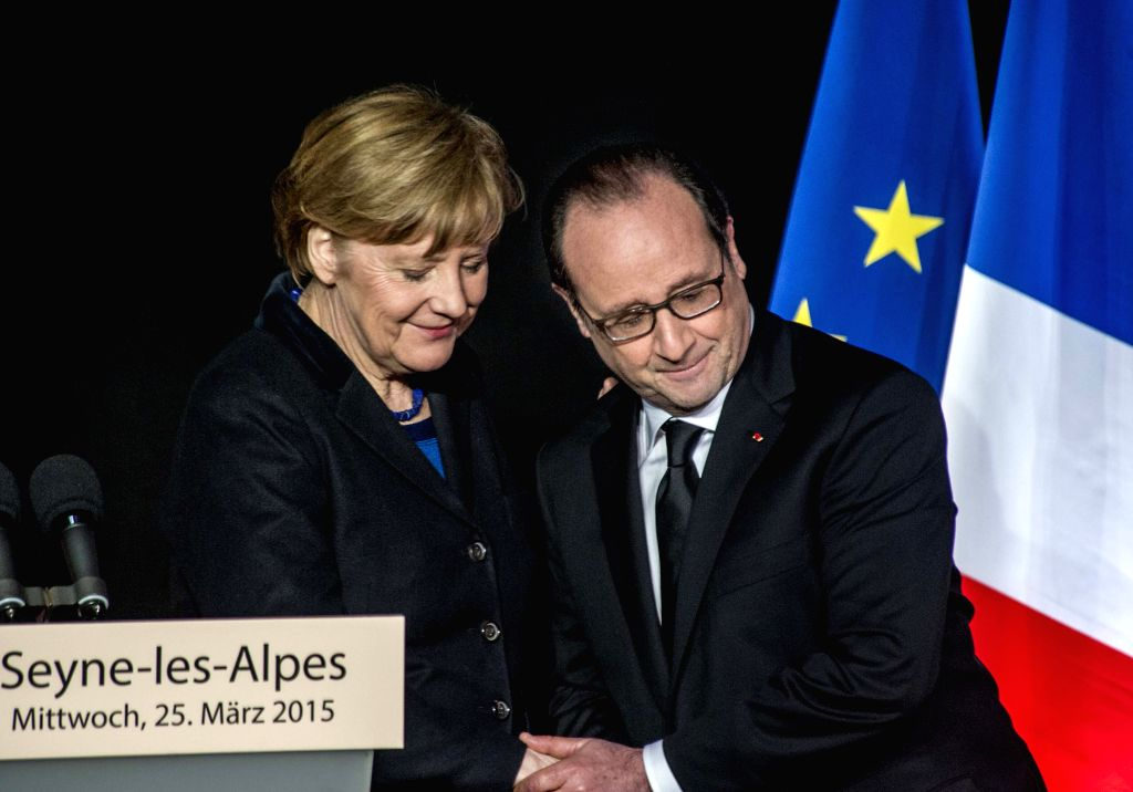 French President Francois Hollande (R) shakes hands with German Chancellor Angela Merkel during a press conference in Seyne-les-Alpes, France, March 25, 2015. ...