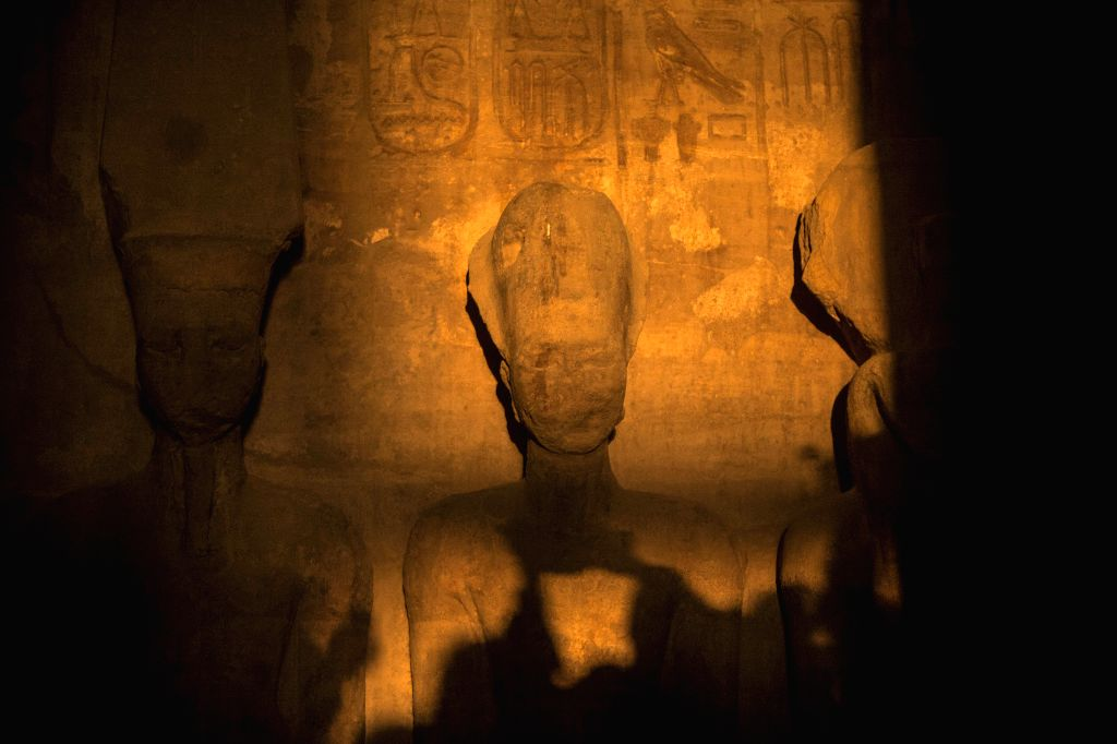 : Shadows of tourists are seen as a ray of light illuminates the statue of Rameses II inside the temple of Abu Simbel, south of Aswan, Egypt, on Feb. 22, 2014. ...