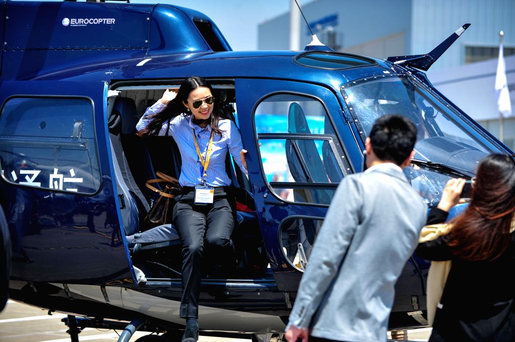 A visitor poses for photos next to an Airbus AS350 Ecureuil business helicopter at the 2014 Asian Business Aviation Conference & Exhibition (ABACE2014) in ...