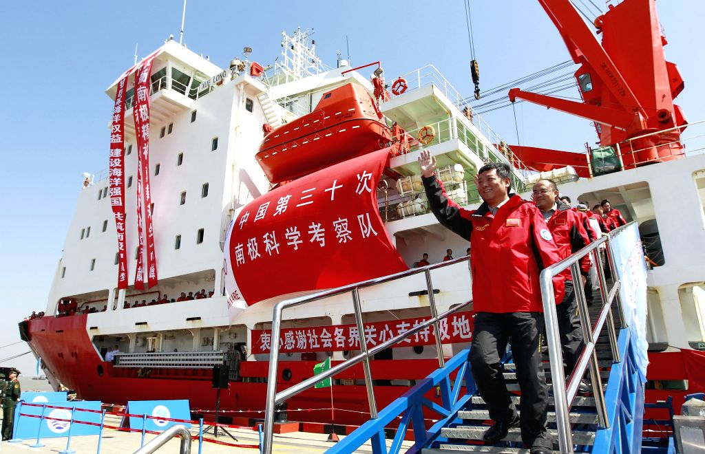 Liu Shunlin (Front), head of China's 30th scientific expedition mission, waves after returning to Shanghai, east China, April 15, 2014. Chinese research vessel ...