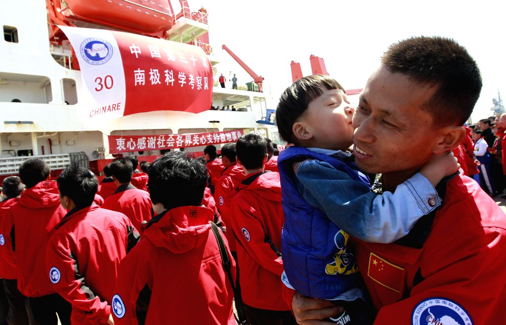 Zhou Jingwu (R), a member of the Chinese scientific expedition team, hugs his son after returning to Shanghai, east China, April 15, 2014. Chinese research vessel
