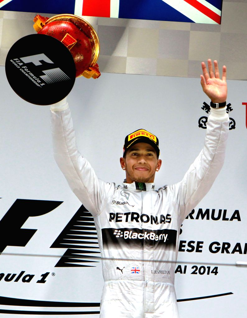 Mercedes AMG Petronas British driver Lewis Hamilton holds the trophy on the podium after winning the the Formula One Chinese Grand Prix in Shanghai, east China, ..