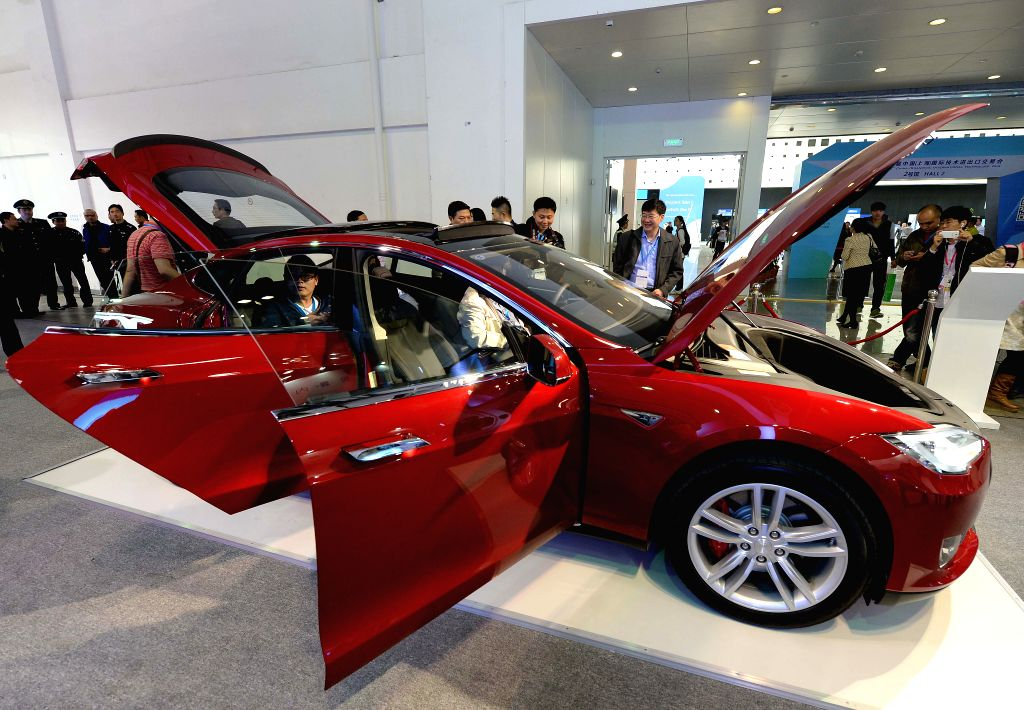 Visitors look at a Tesla vehicle during the 2nd China Shanghai International Technology Fair (CSITF) in east China's Shanghai, April 24, 2014. Tesla Motors is an .