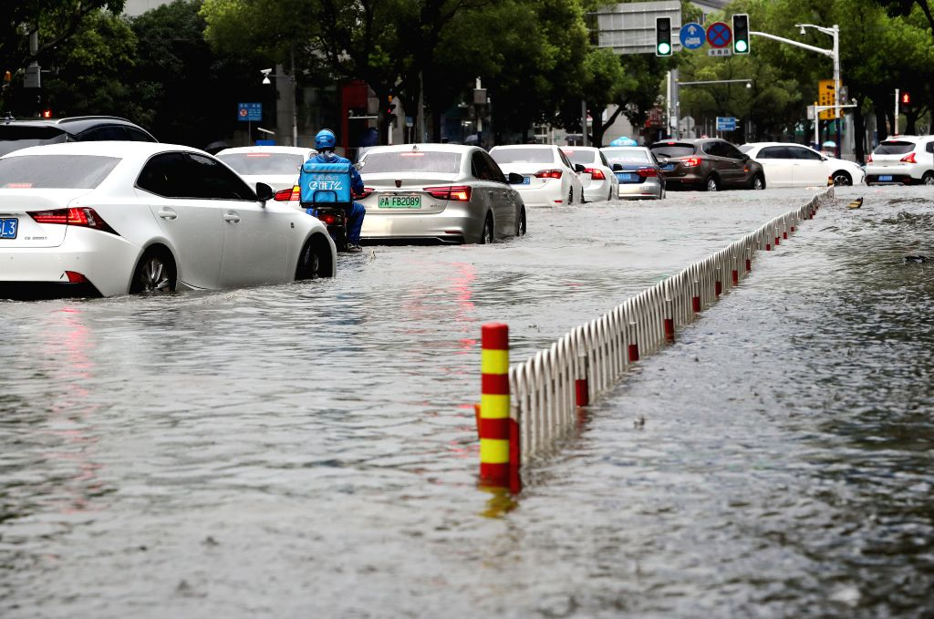 SHANGHAI, Aug. 10, 2019 - Cars are seen on flooded Xinsong Road in Shanghai, east China, Aug. 10, 2019. The Shanghai central meteorological station updated the yellow alert for heavy rain to orange ...