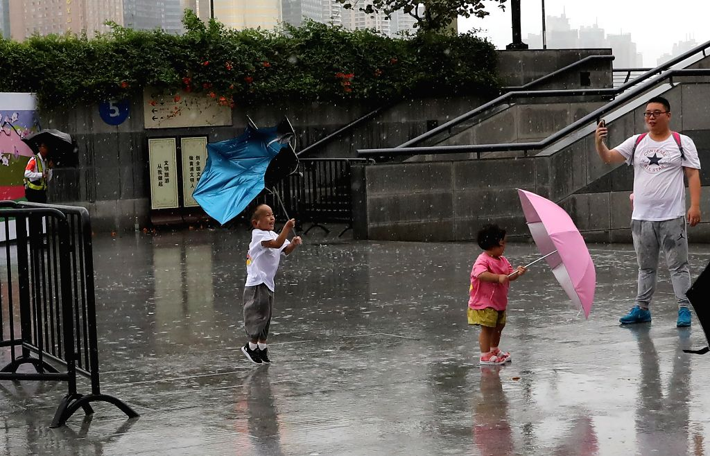 SHANGHAI, Aug. 10, 2019 - Children play in the rain at Waitan area in Shanghai, east China, Aug. 10, 2019. The Shanghai central meteorological station updated the yellow alert for heavy rain to ...
