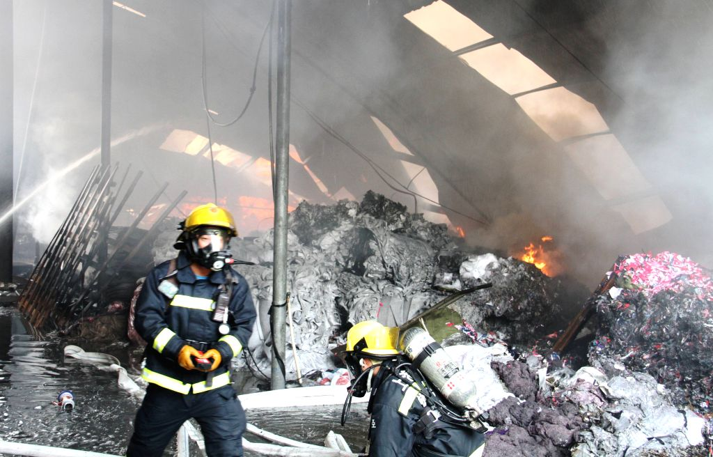Firemen work at a burning factory in the Jinshan District in Shanghai, east China, Dec. 29, 2014. No casualties were reported after the fire. (Xinhua/Zhu ...