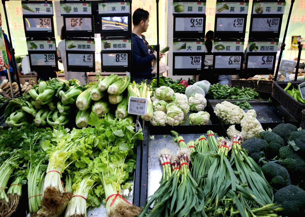 SHANGHAI, March 9, 2017 - A consumer selects vegetables at a supermarket in Shanghai, east China, March 7, 2017. China's consumer price index (CPI), a main gauge of inflation, advanced 0.8 percent ...