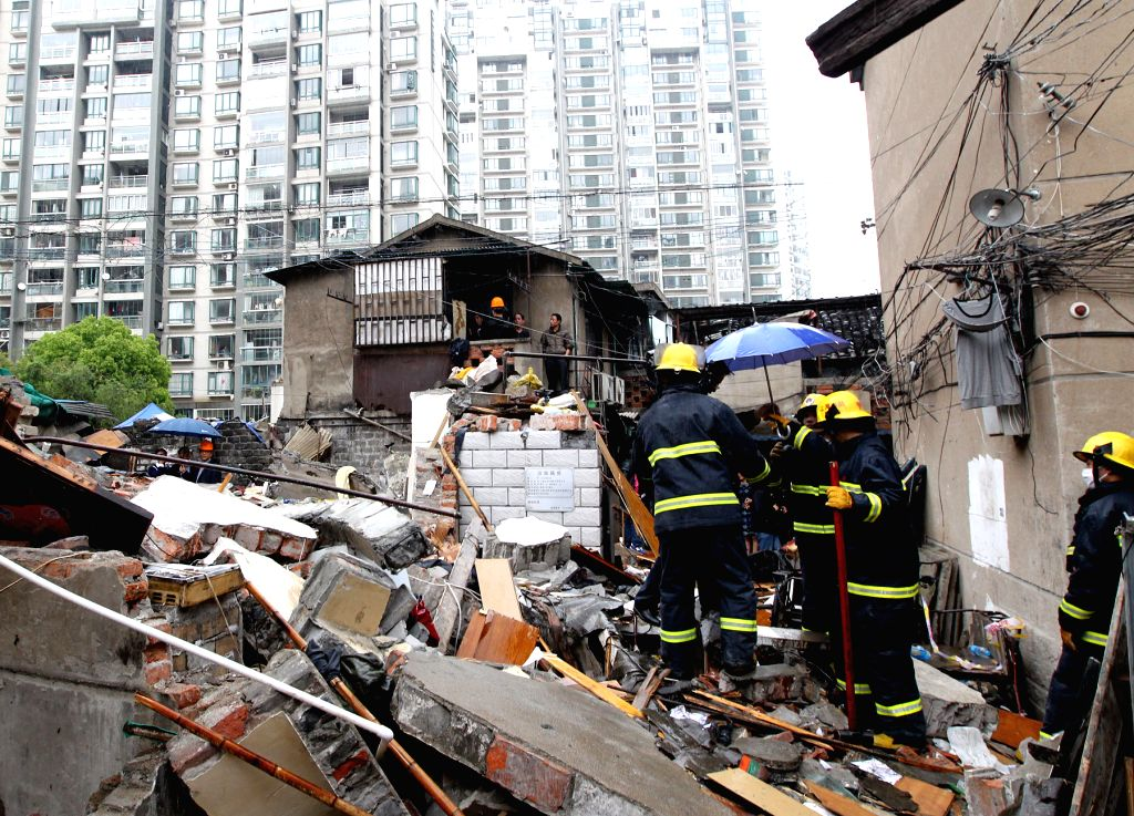 Rescuers work at the accident site of a collapsed building in the Hongkou District of Shanghai, east China, May 4, 2014. Two people have been confirmed dead and ...