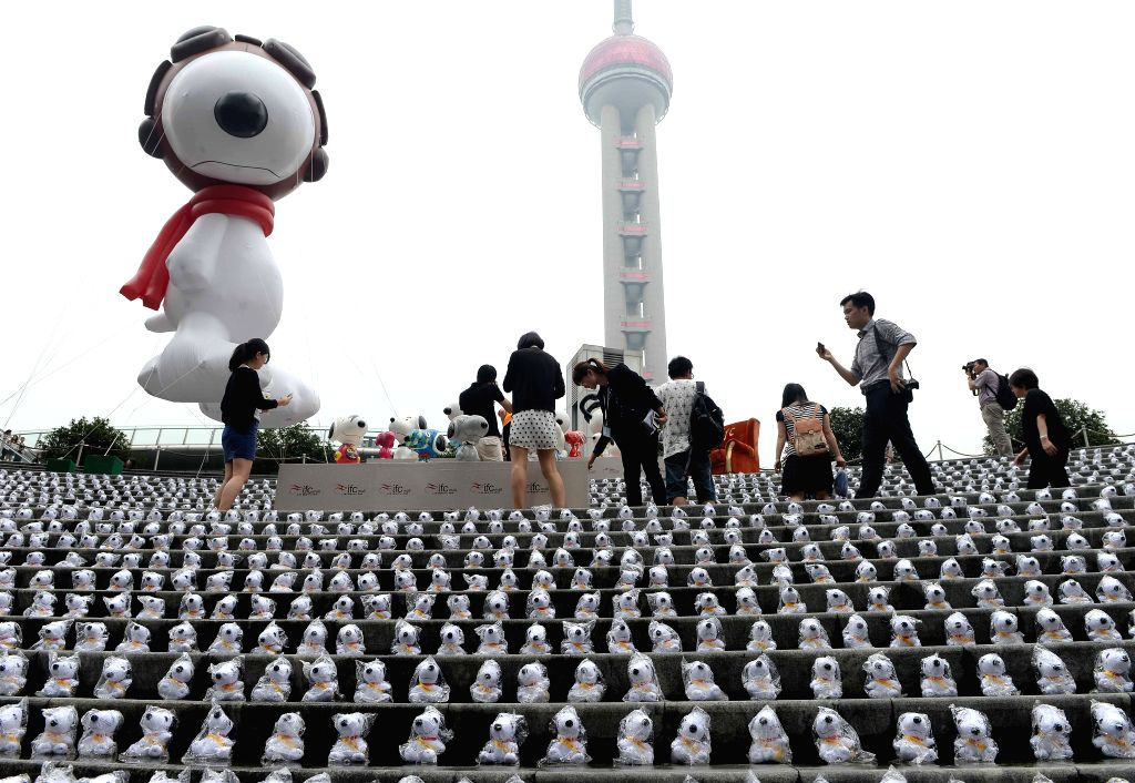 Visitors look at Snoopy dolls presented during an exhibition of Snoopy in Lujiazui District of Shanghai, east China, Sept. 3, 2014. An eight-meter-tall Snoopy ...
