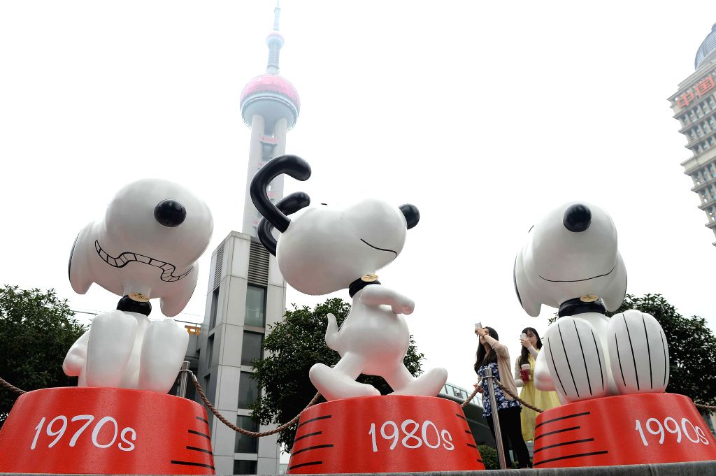 Visitors take photos of Snoopy statues during an exhibition of Snoopy in Lujiazui District of Shanghai, east China, Sept. 3, 2014. An eight-meter-tall Snoopy ...