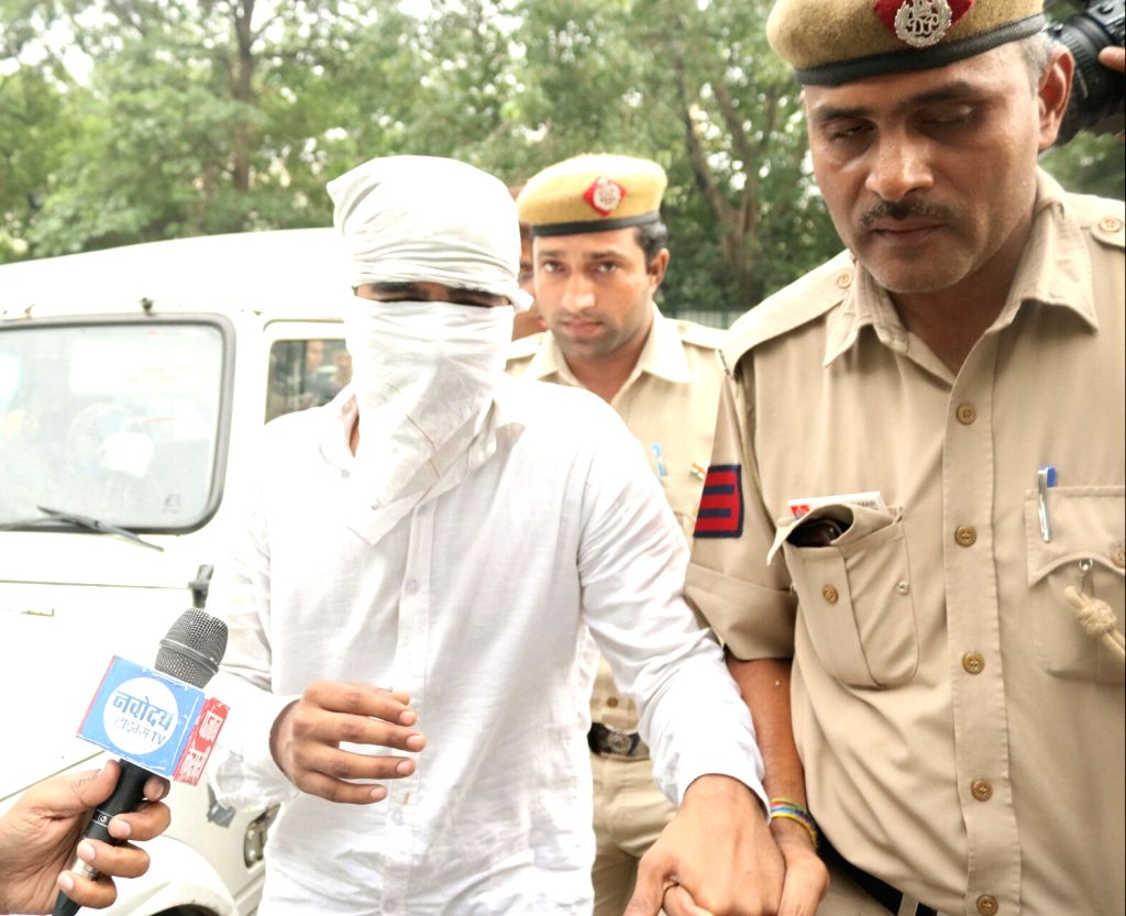 Shekhar, an accused in E-rickshaw driver murder case being taken away by police in in New Delhi, on May 31, 2017.