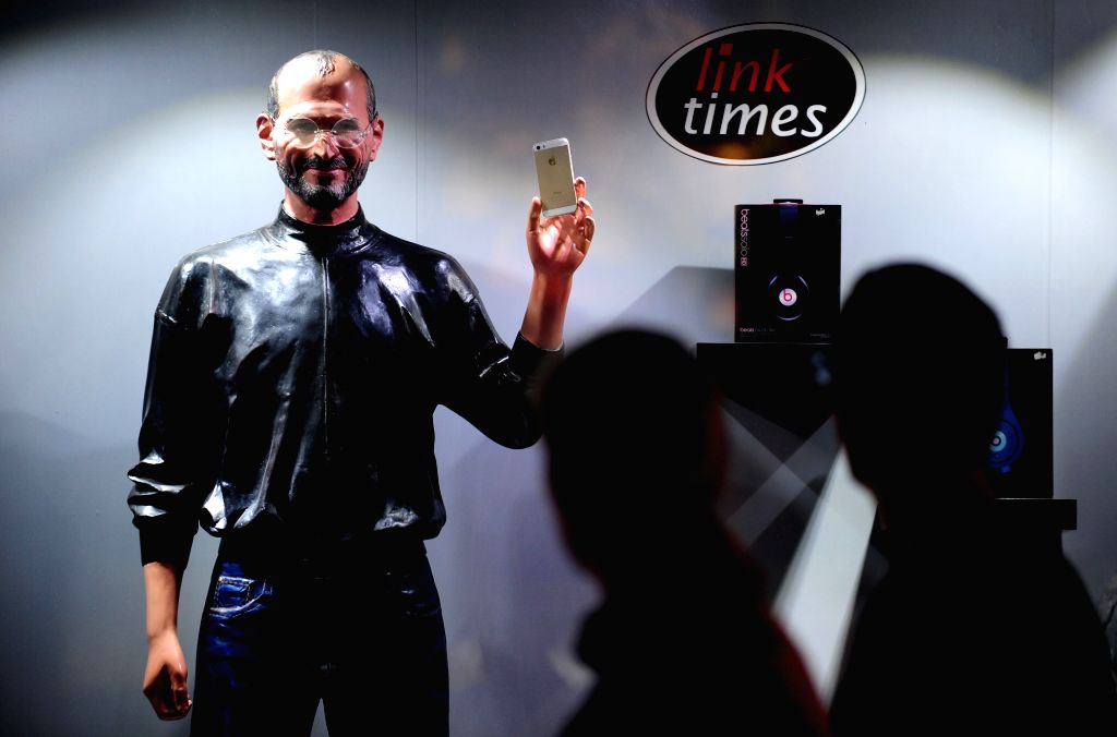 People walk past a wax statue of Steven Jobs at an Apple store in Taiyuan Street in Shenyang, northeast China's Liaoning Province, Aug. 18, 2014.