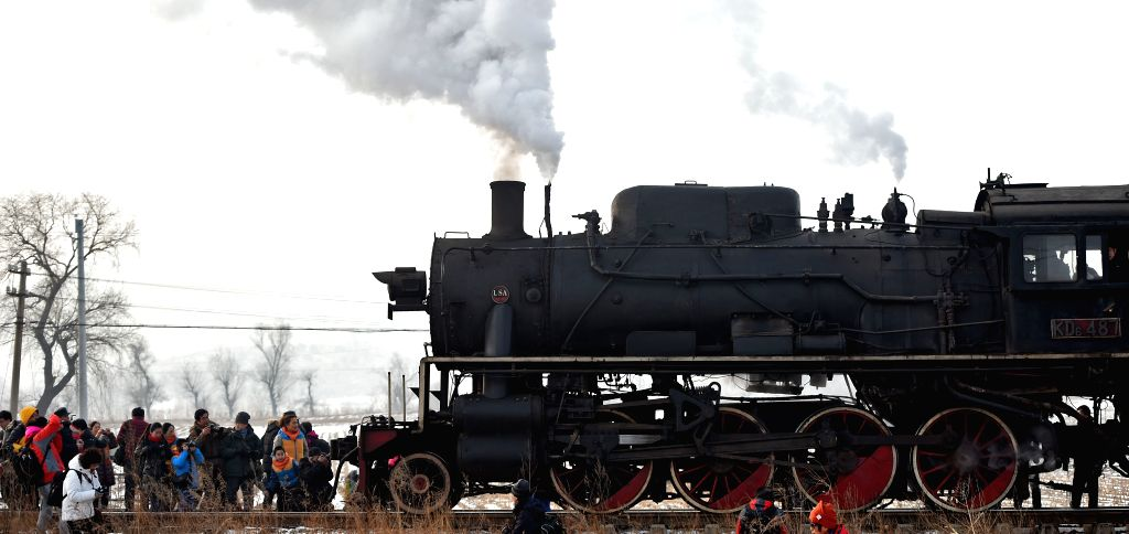 Tourists take photos as a steam locomotive passes through during the China 8th International Steam Locomotive Fair held in Diaobingshan city, northeast China's ...