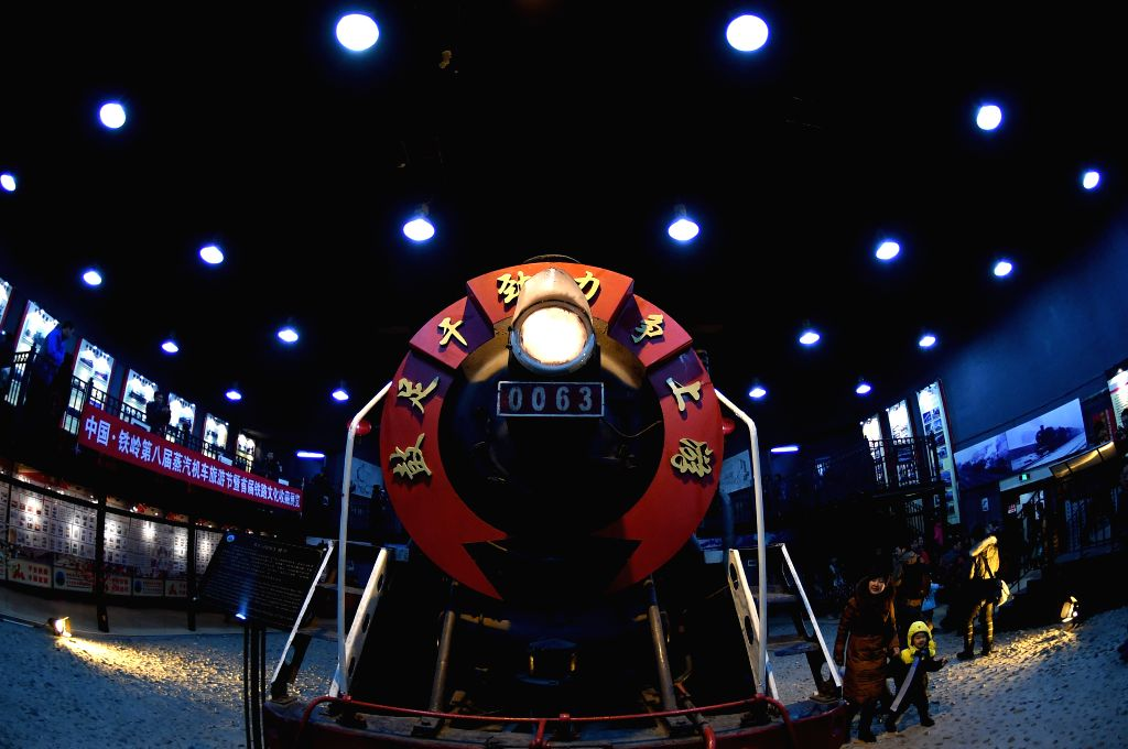 Tourists view a steam locomotive during the China 8th International Steam Locomotive Fair held in Diaobingshan city, northeast China's Liaoning Province, Jan. 24, .