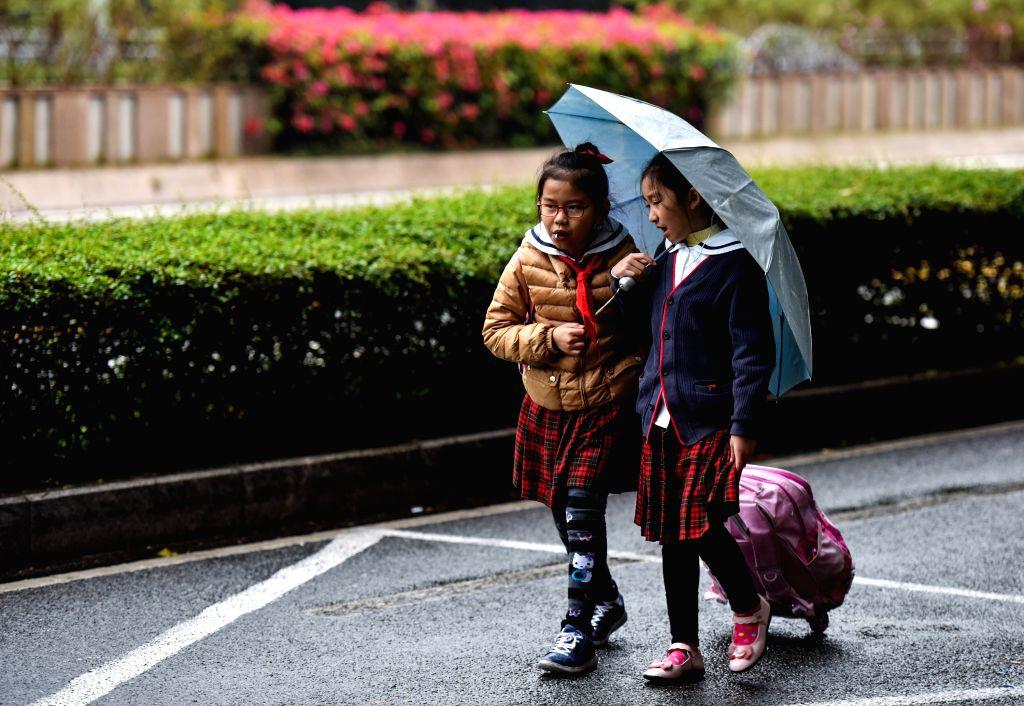 Children walk in the rain in Shenzhen, south China's Guangdong Province, Jan. 12, 2015. Cold air began to affect most regions in Guangdong from Jan. 12, according .