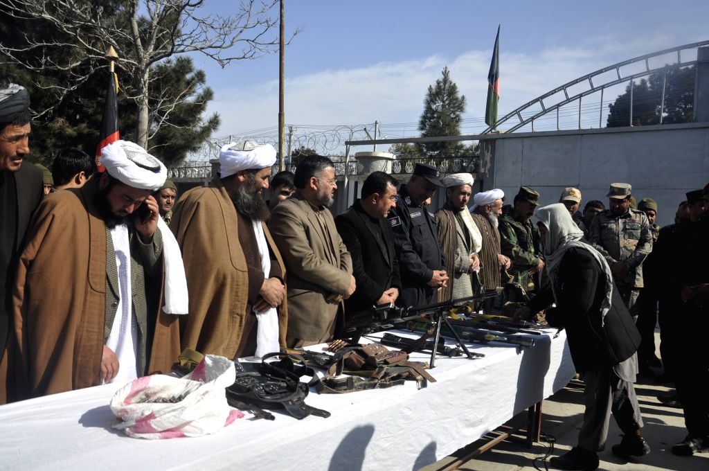 SHIBERGHAN, Feb. 12, 2018 - An anti-government militant member (R front) hands over his weapon to local officials during a surrender ceremony in Shiberghan city, capital of Jawzjan province, ...