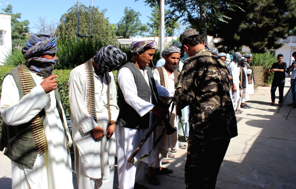 SHIBERGHAN, June 18, 2016 - A militant hands over his weapon to a local official during a surrender ceremony in Sheberghan, capital of northern Jawzjan province, Afghanistan, June 18, 2016. Some 15 ...