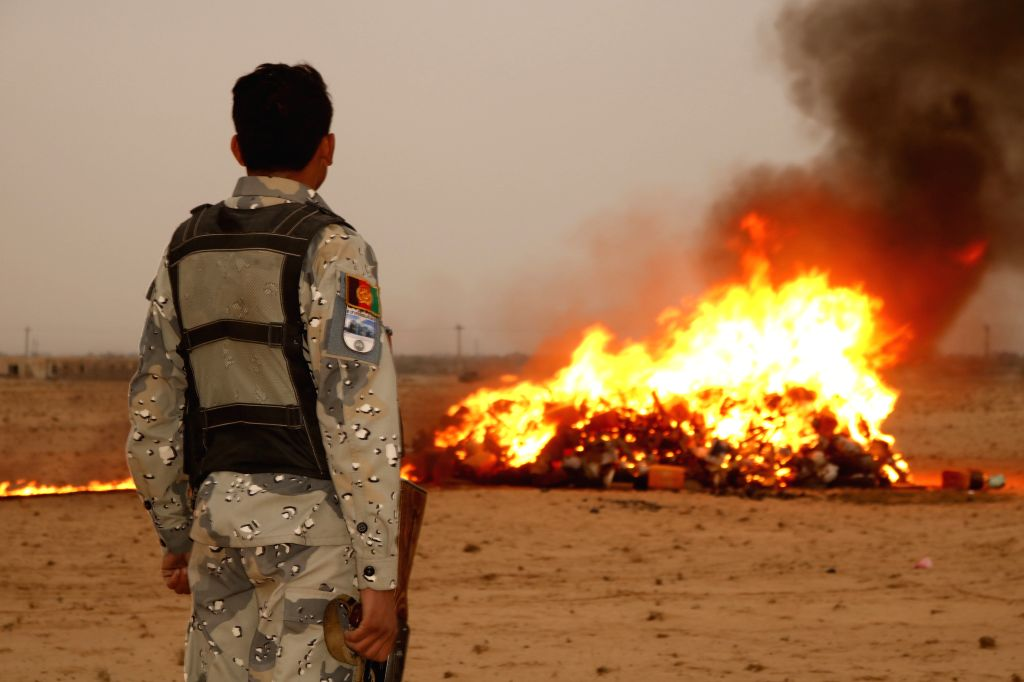 SHIBERGHAN, Nov. 1, 2018 - An Afghan security force member stands beside burning drugs in Shiberghan city, capital of Jawzjan province, Afghanistan, Oct. 30, 2018. Afghan authorities burned on ...