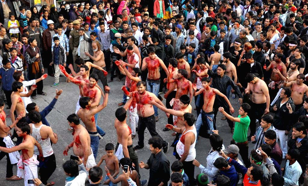 Shiite Muslims flagellate themselves during a procession to mark the completion of 40 days of mourning after Yaum-e-Ashura in Jaipur on Dec.24, 2013. (Photo: Ravi Shankar Vyas/IANS)