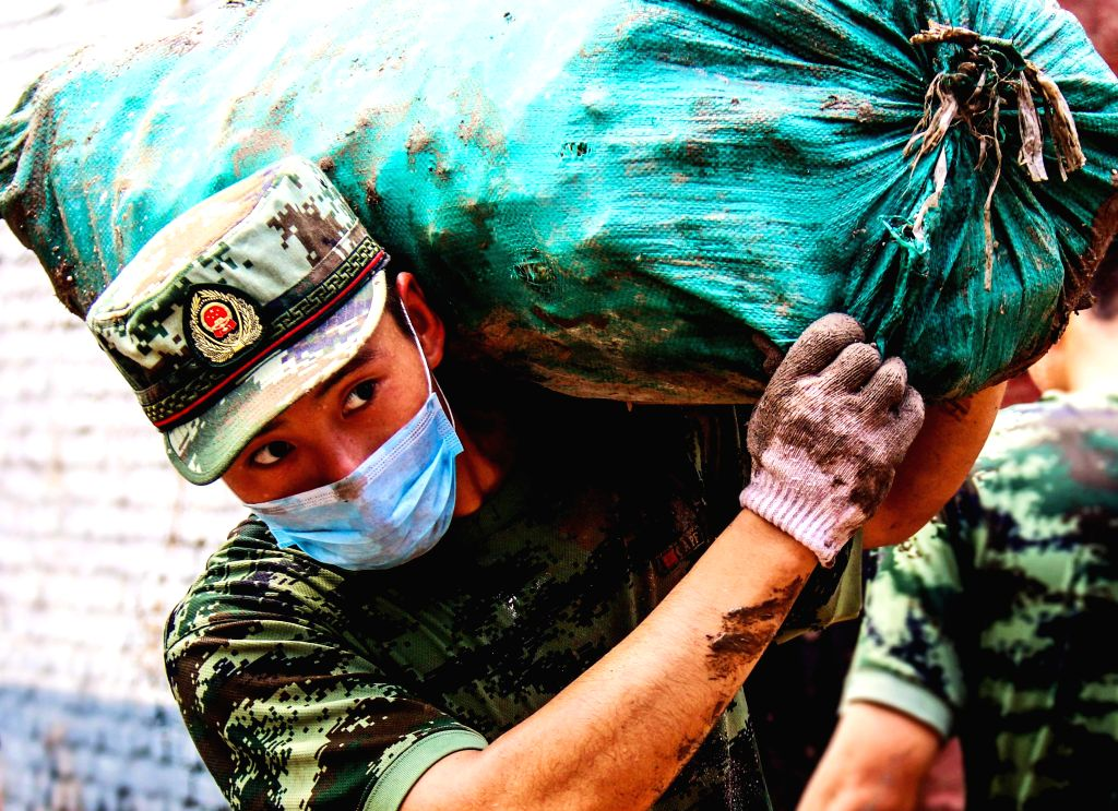 SHIJIAZHUANG, Aug. 4, 2016 - A soldier carries a bag of materials during a campaign to fight against flood in Nanshimen Village of Xiaozuo Township in Jingxing County, north China's Hebei Province, ...