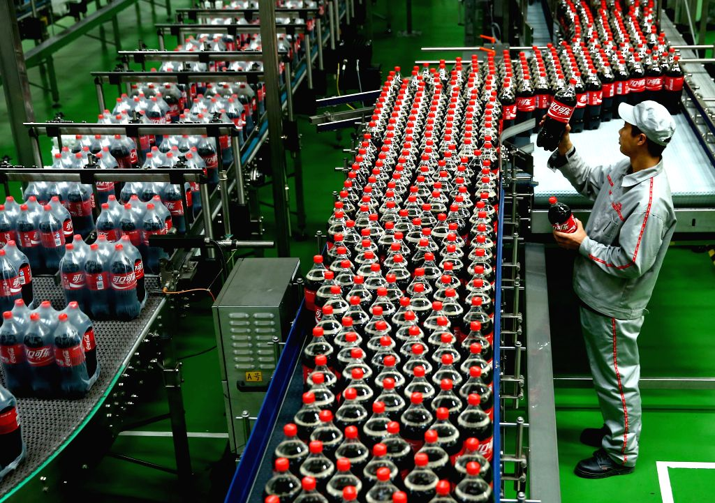 SHIJIAZHUANG, Oct. 24, 2013 (Xinhua/IANS) -- A worker checks the package at the new plant of Coca-Cola in Shijiazhuang, capital of north China's Hebei Province, Oct. 24, 2013. Coca-Cola has established 43 plants all over China, and the one in Hebei i