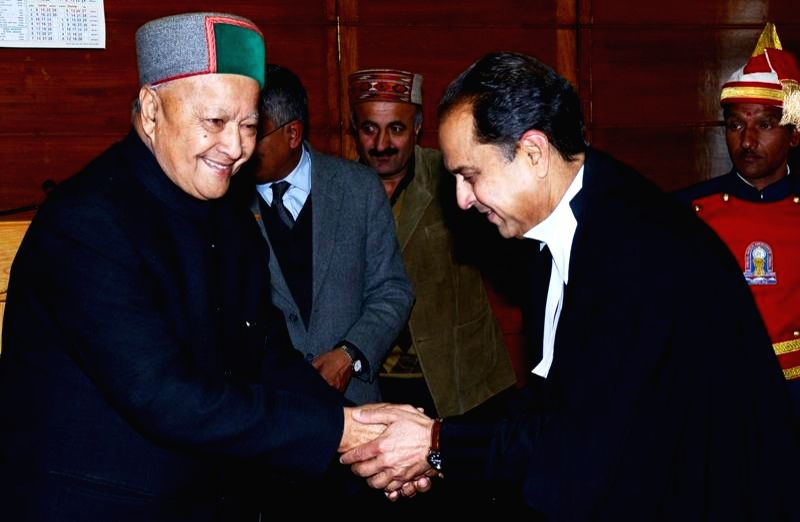 Himachal Pradesh Chief Minister Virbhadra Singh greets the new chairman of the state administrative tribunal Justice V. K. Sharma, who assumed office in Shimla on Feb 27, 2015. - Virbhadra Singh