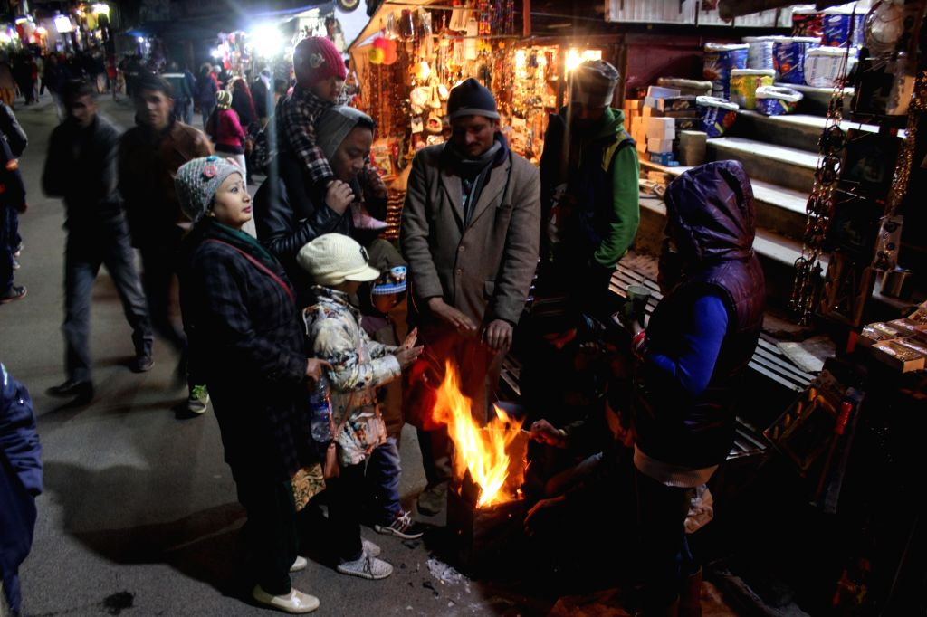 Shimla: People warm themselves around a fire on a cold evening in Shimla on Jan 3, 2017. (Photo: IANS)