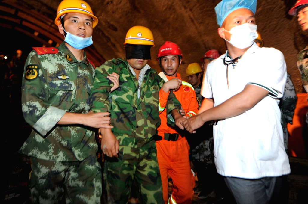 A rescued worker walks out of a rescue passage in a collapsed tunnel in Shiqian County, southwest China's Guizhou Province, Aug. 16, 2014. Thirteen workers were ...
