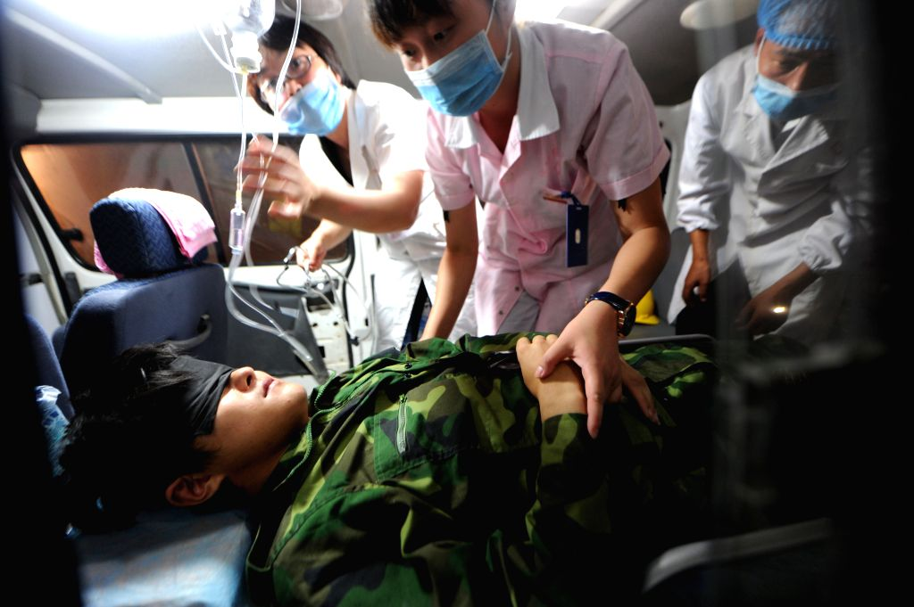 Medical workers treat a rescued worker on an ambulance in Shiqian County, southwest China's Guizhou Province, Aug. 16, 2014. Thirteen workers were successfully ...