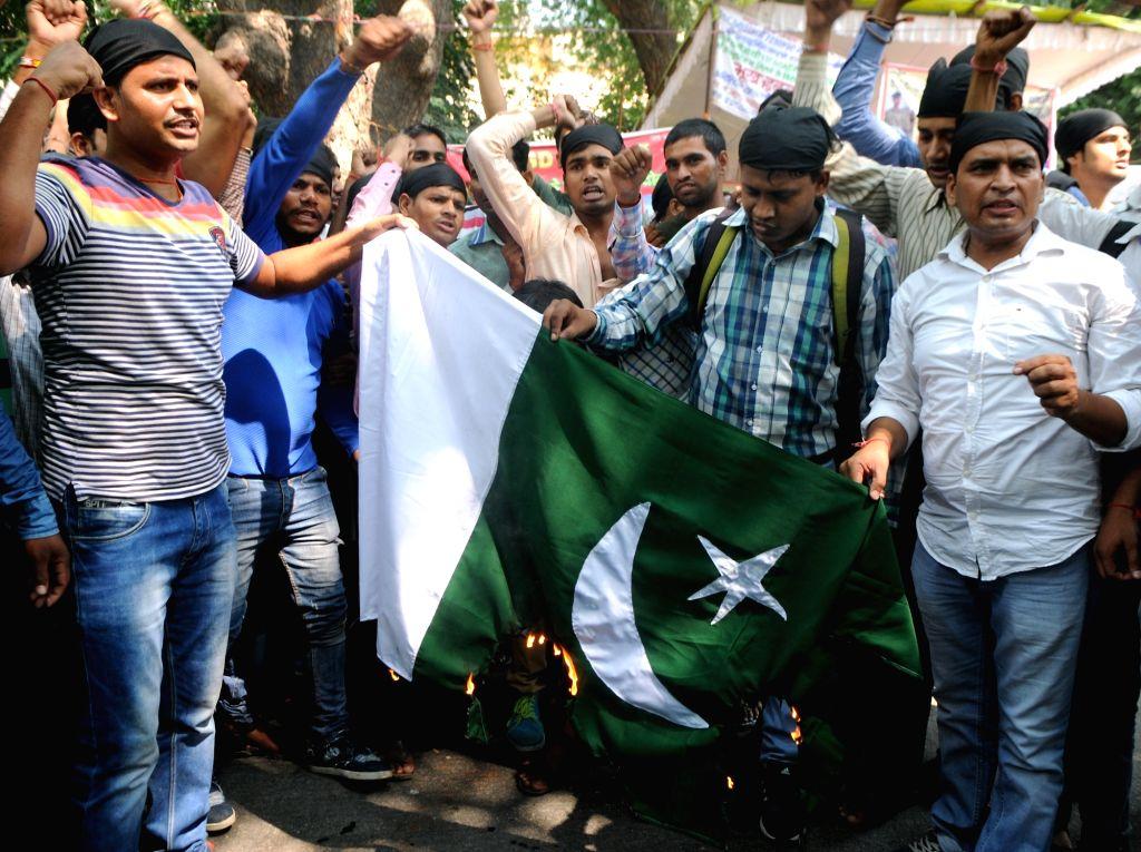 Shiv Sena activists burn Pakistan flag in New Delhi protesting terror attack on Uri army camp on Sept 19, 2016.