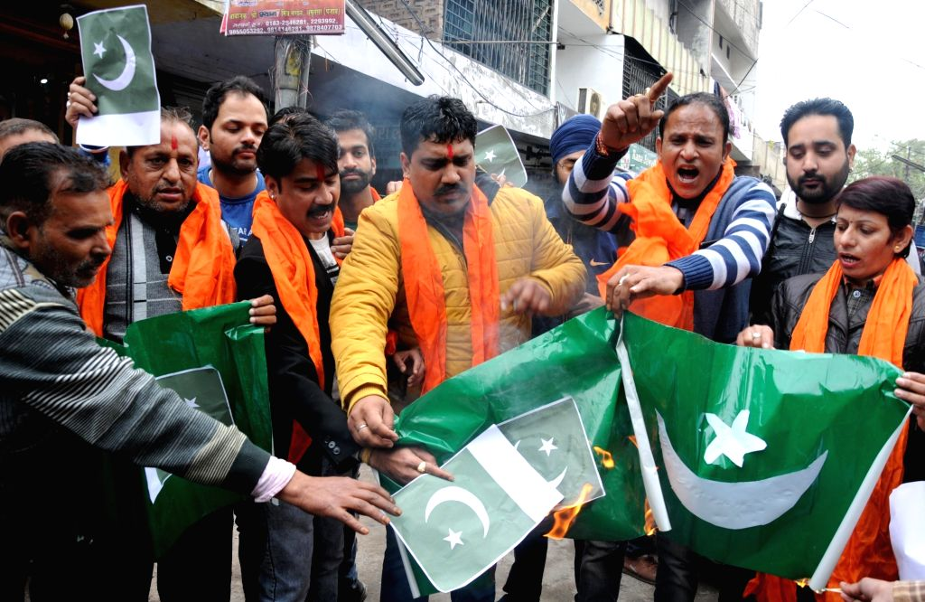 Shiv Sena workers burn Pakistan flag during a protest against suicide attack on a CRPF bus in Jammu and Kashmir's Pulwama district in which atleast 45 soldiers lost their lives; in Amritsar ...