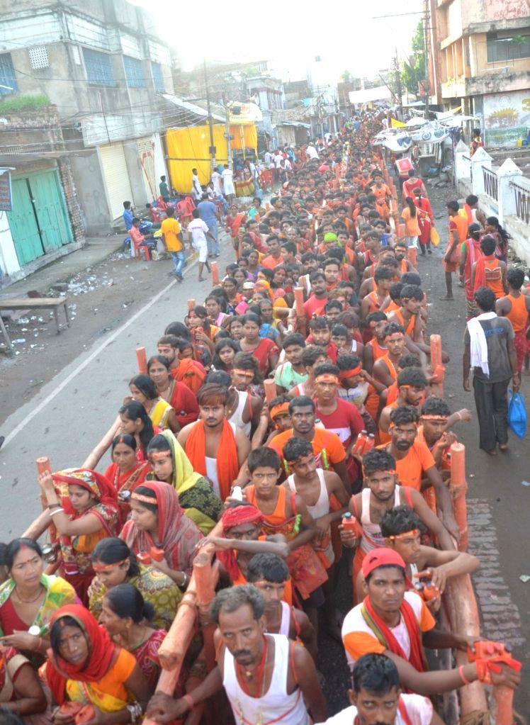 Shiva devotees or 'Kanwariyas' wait in queues to perform 'Jala Abhishek' of Lord Shiva outside Baba Garibnath Dham on 'Sawan Shivratri' during the Hindu holy month of Shravan, in Bihar's ...
