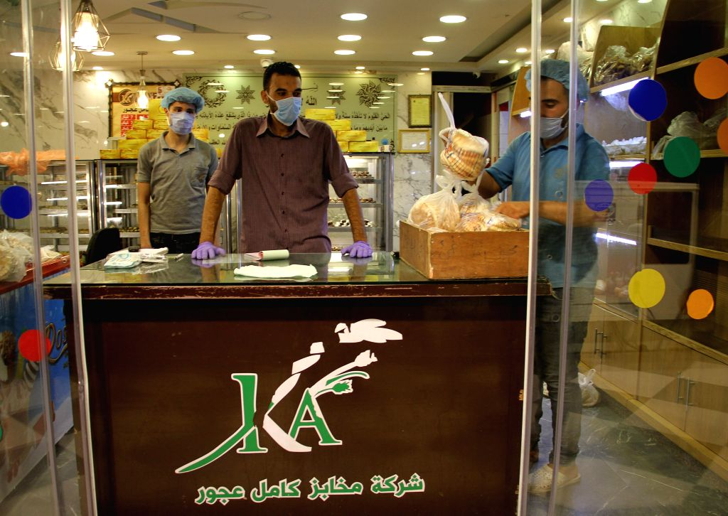 Shop assistants wearing face masks work in a bakery in Gaza City, Aug. 28, 2020. Palestine recorded two deaths and 724 new COVID-19 cases in the Palestinian ...