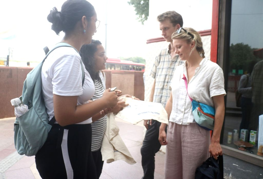 Shulabh international volunteers distribute cotton carry bags to people to avoid plastic during a social campaigning 'Say No To single use Plastic' in New Delhi on Sep 12, 2019.