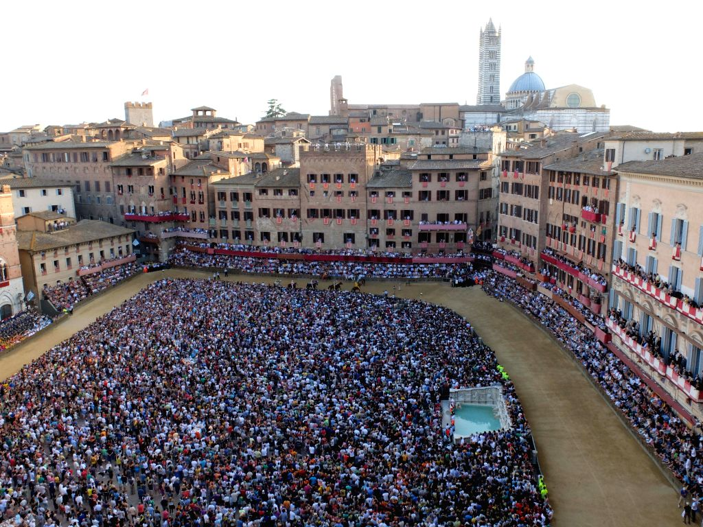 """Spectators watch the horse race in Siena, Italy, July 2, 2014. A traditional horse race, known as """"Palio di Siena"""" in Italian was held in Italian historical ."""