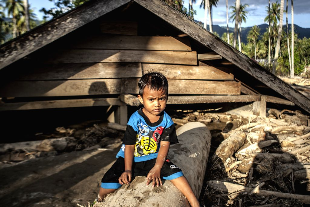 SIGI, May 1, 2019 - A boy sits on a wood in front of a house covered by mud after flood at Bangga village in Sigi, Central Sulawesi, Indonesia. May 1, 2019. Heavy rainfall in Sigi regency, Central ...