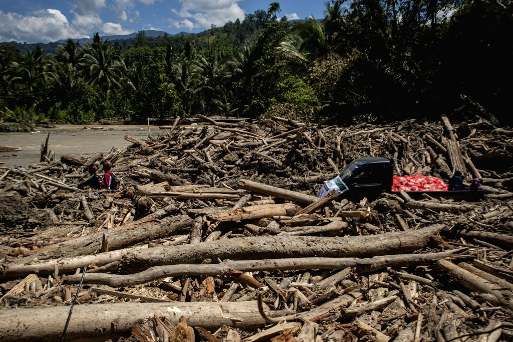 SIGI, May 4, 2019 - Vehicles run past wood debris on both sides of a road after a flood hit Tuva village in Sigi Regency, Central Sulawesi, Indonesia, May 4, 2019. Heavy rainfall in Sigi Regency, ...