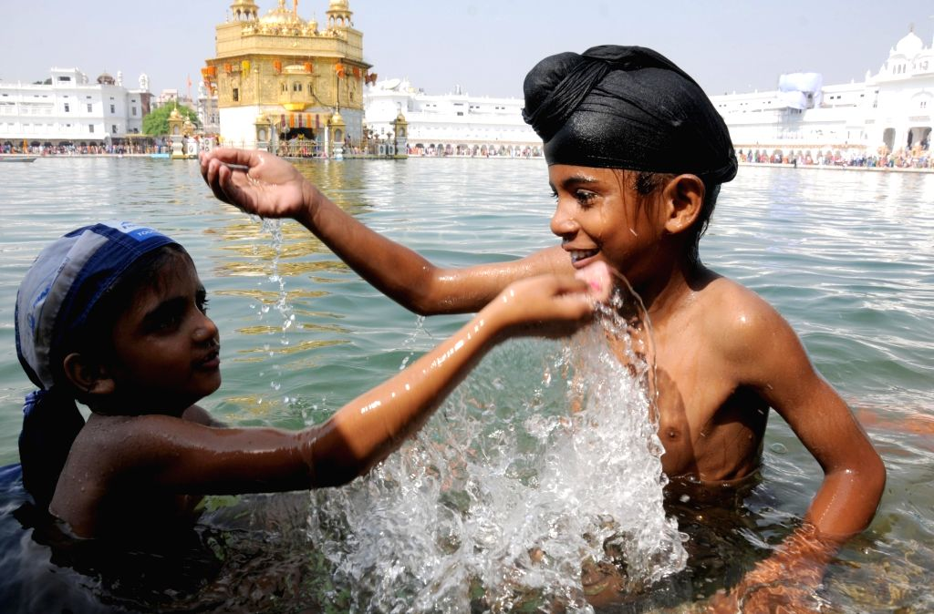 Sikh devotee take holy dip in the sacred pond of the Golden Temple on the occasion of the fourth Sikh Guru Ramdas' birth anniversary in Amritsar, on Oct 17, 2016.