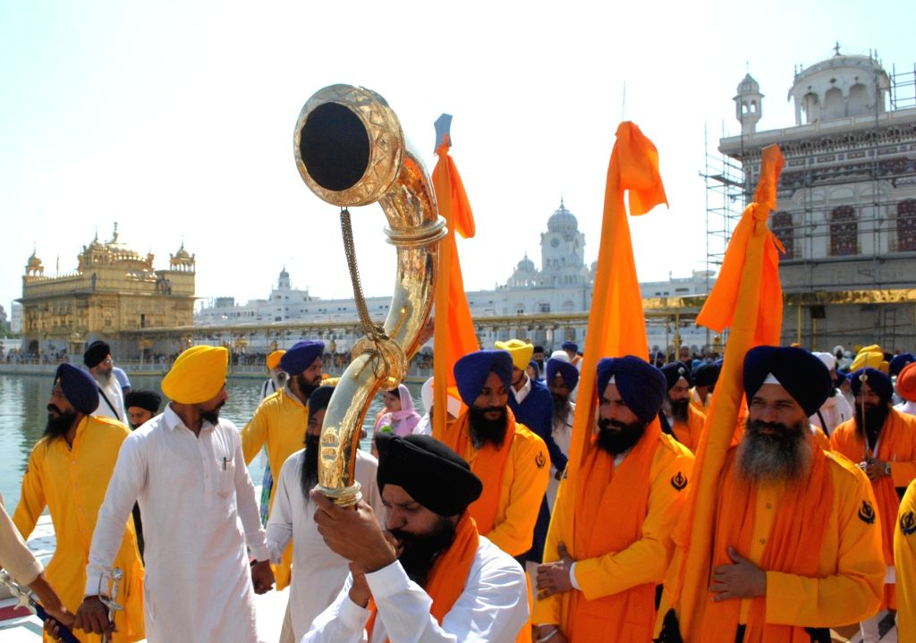 Sikh devotees carrying palanquin during a religious procession in the parikarma of the Golden Temple on the eve of the birth anniversary of Forth Sikh Guru Ramdass Ji (Founder of Amritsar ...