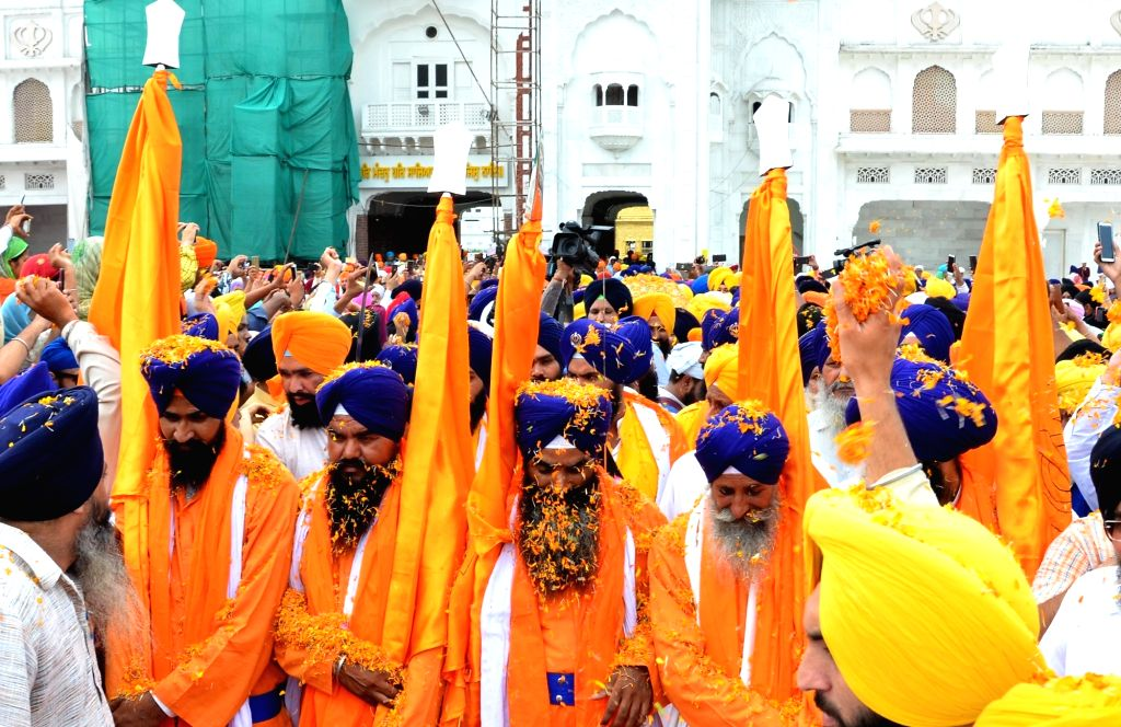 Sikh devotees participate in 'Nagar Kirtan' (religious procession) that is on its way to the Dera Baba Nanak in Punjab's Gurdaspur district, organised to mark the 550th birth anniversary of ... - Nanak Dev
