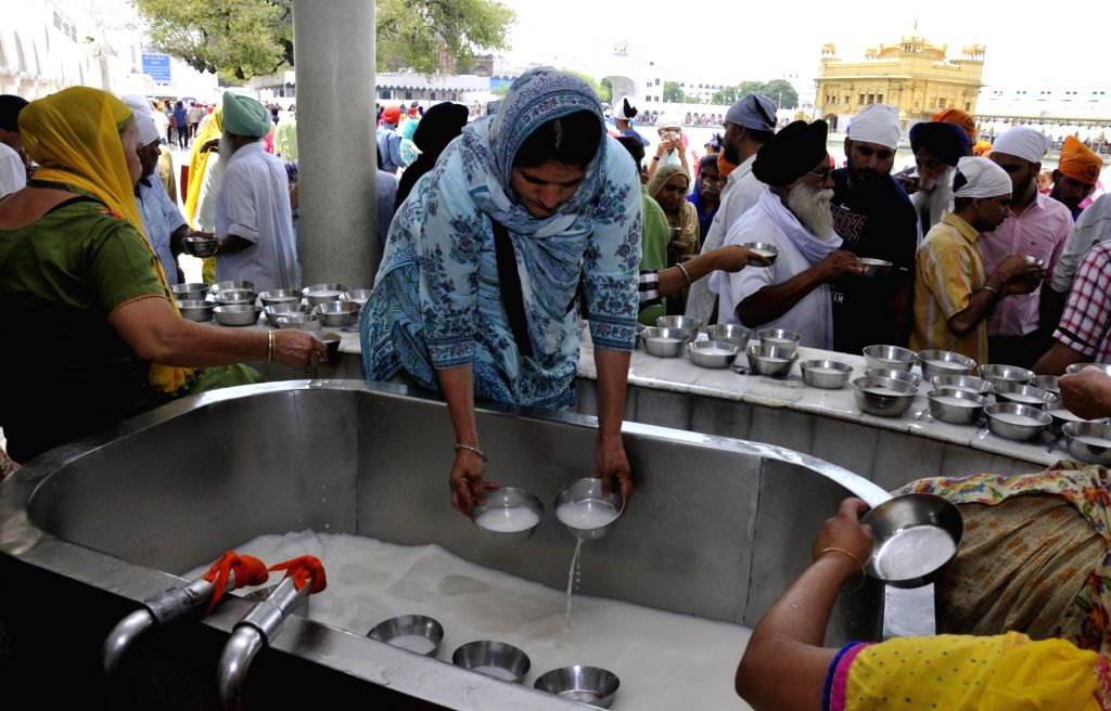 Sikh devotees serve  sweet drinks at a 'Chabeel', put up at Golden Temple on the eve of martyrdom day of Guru Arjan Dev in Amritsar on May 29, 2017. - Arjan Dev