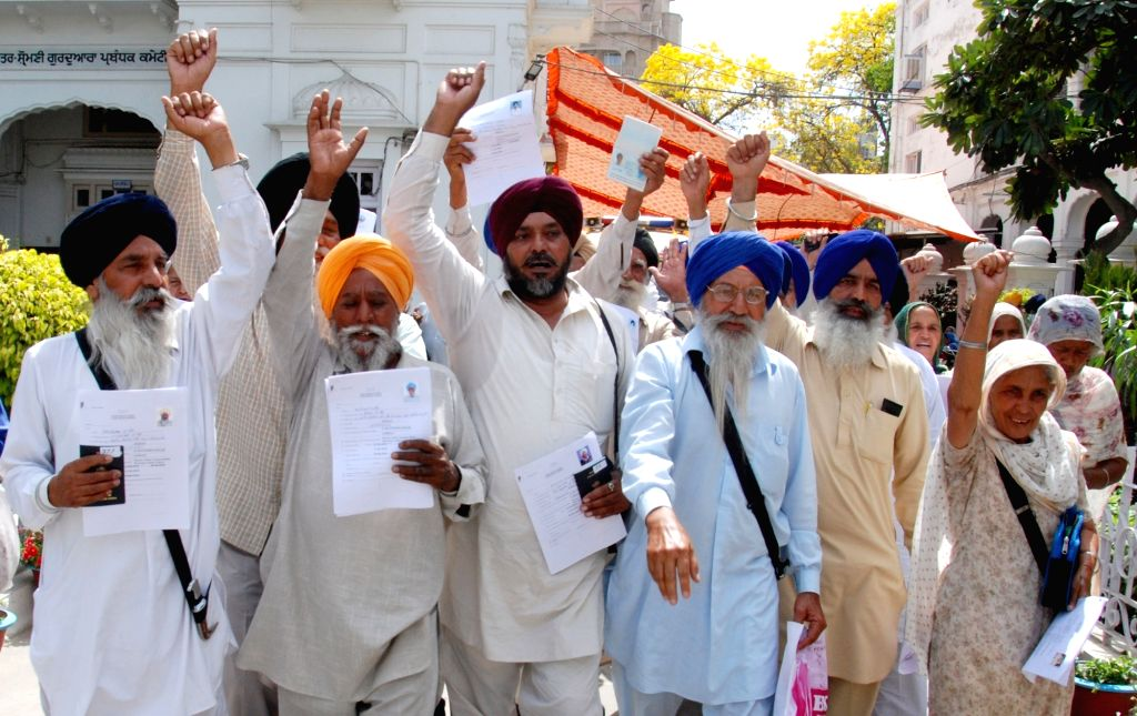 Sikh devotees show their passports after collecting them from the Shiromani Gurdwara Parbandhak Committee (SGPC) after getting approval to travel to Pakistan for Baisakhi celebrations, in ...