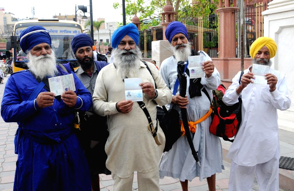 Sikh devotees show their passports as they leave for Pakistan to celebrate Baisakhi, from Amritsar on April 12, 2019.