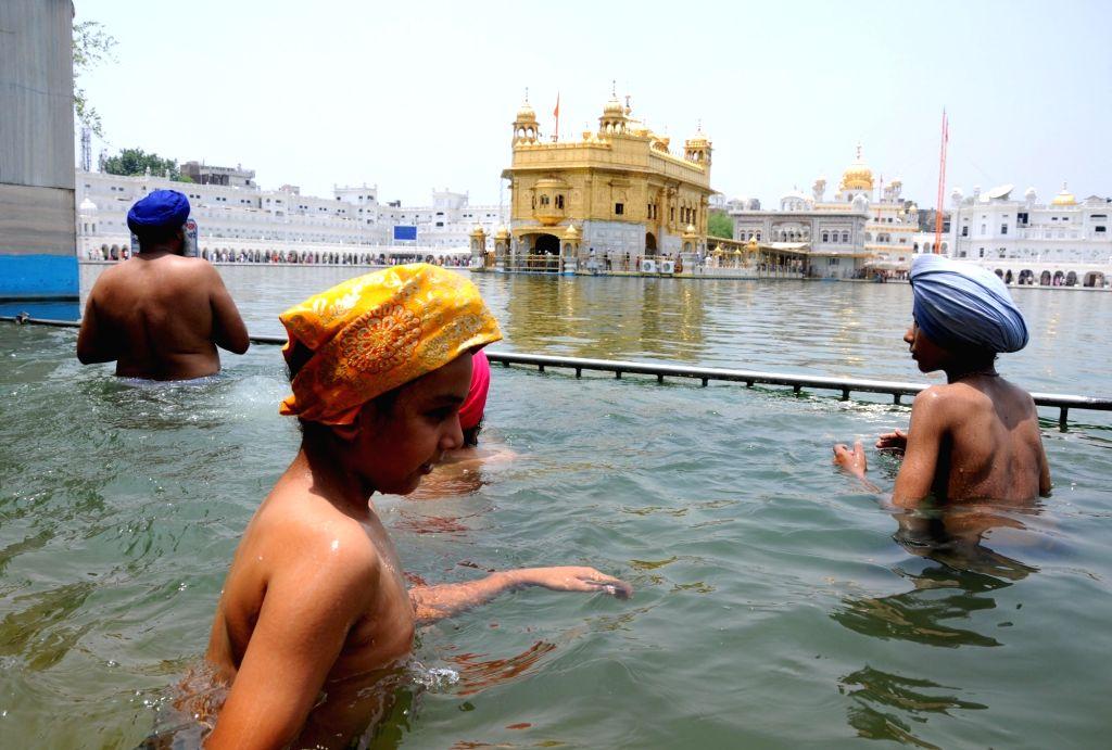 Sikh devotees take a dip in the holy pond at the Golden Temple on 'Gurta Gadhi Diwas' of sixth Sikh Guru, Guru Hargobind in Amritsar on June 7, 2018.