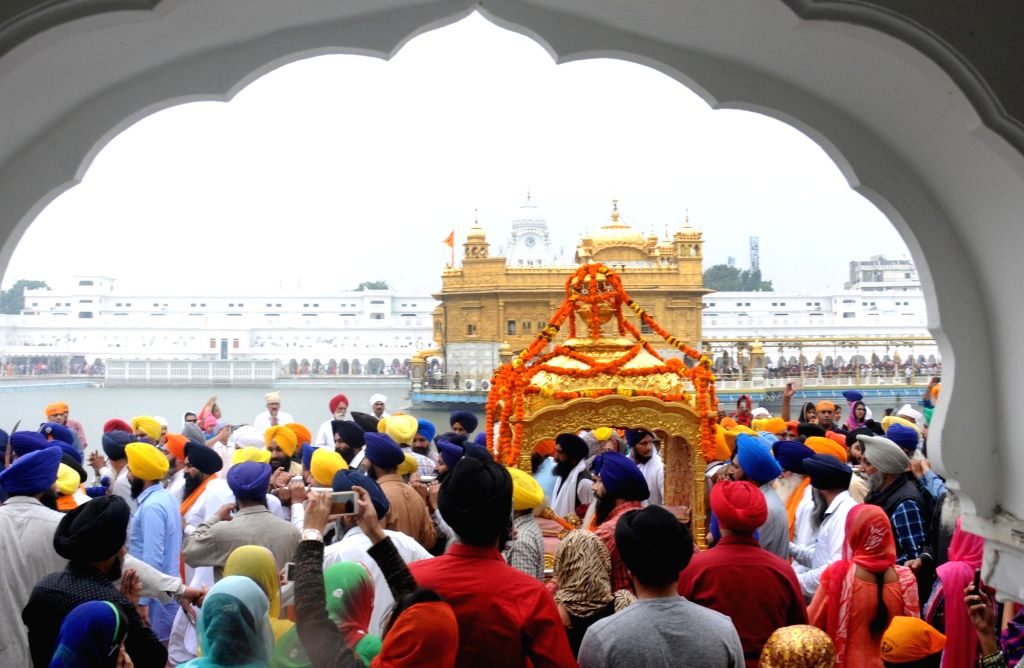 Sikh devotees taking part in a religious procession at Golden Temple in Amritsar ahead of 548th birth anniversary of Sri Guru Nanak Dev on Nov. 12, 2016.
